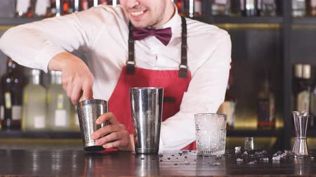 red tie : Barman wearing the bow tie, white shirt and red apron makes cocktail at bar counter at restaurant.