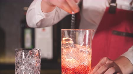vermouth : Bartender using long metal spoon to mix ice cubes with drink in a glass standing at wooden bar counter Stock Footage