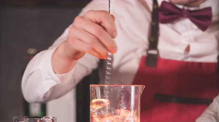 bourbon whisky : Barman mixing cocktail ingredients with a long spoon in high glass filled with ice cubes on the bar counter