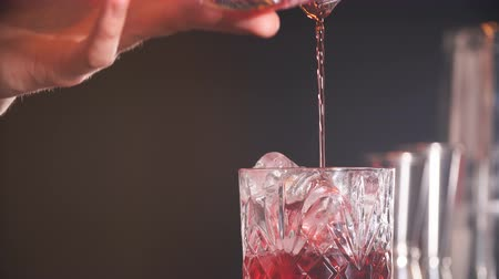 шейкер : The bartender man pours ruby cocktail into crystal glass, close up. Bar, Restaurant Beverage and Service concept.