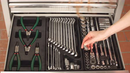 peças : Female Mechanic Taking Instruments From Toolbox in Repair Garage