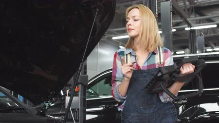 belső : Pleasant blond girl using an automotive diagnostic scanner. Stock mozgókép