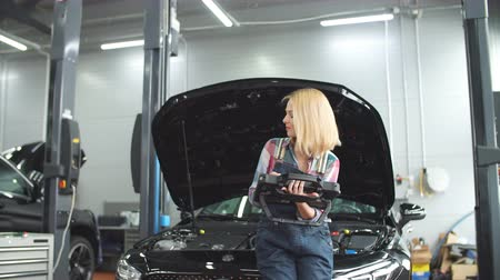 пожилые : Pleasant blond girl using an automotive diagnostic scanner. Стоковые видеозаписи