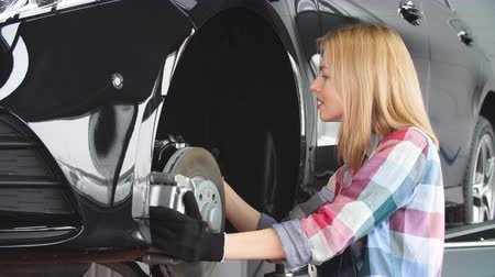 substituição : Woman is changing replacing brakes. Occupation, lifestyle, unusual job for women