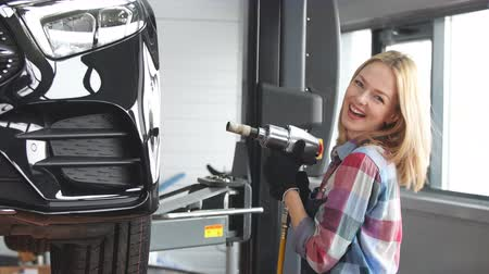 overall : Blond girl screwing car wheel at the garage. Working day