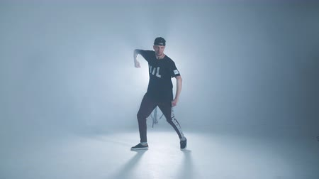 tokmak : Sporty modern style hip-hop dancer dressed in urban style wear shows his dance on blue studio background.