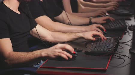 piada : Group of adult male and female gamers sitting in a row behind the monitors, play in PC gaming centre. Humor, joke concepts. Funny angry man having some computer problems. Frustration concept Stock Footage
