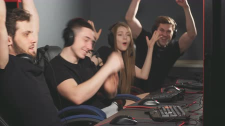 krachtig : Joyful young people sitting at powerful computers in gaming centre and giving high five triumphantly, celebrating victory in game. Stockvideo