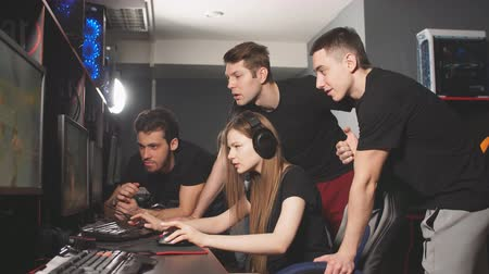 стратегический : Group of male gamers gather around the female player, thinking hard about game strategy playing in cyber games tournament. Стоковые видеозаписи