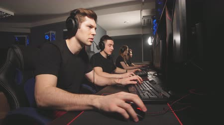 удивительный : Team of gamers in headphones emotionally rejoices in victory playing in e-sport club, looks at the computer screen and enjoying their triumph. Стоковые видеозаписи