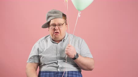 nevetséges : Portrait of offended adult middle-aged man in grey casual wear, crying like a child and wiping tears with hand, holding air balloons on pink background