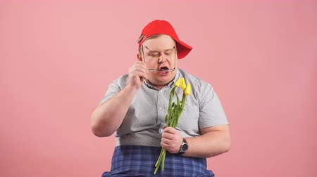 nevetséges : Portrait of hesitating young man in grey t-shirt and red cap waiting for girlfriend with flowers, being afraid that she would not come