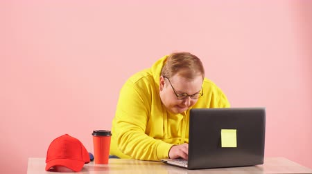 nerd : Funny plump man in yellow sweatshirt having foolish face expression using laptop with funny freak grimace
