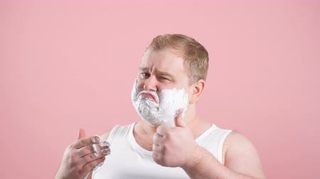 nevetséges : Cropped shot of upset man with gel on cheeks, has sad expression, sensitive skin, man going to shave his chin despite ofskin irritation, isolated over pink background.