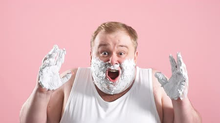 shaving foam : Upset man with gel on cheeks, has sad expression, sensitive skin, man going to shave his chin despite ofskin irritation, isolated over pink background, slow motion. Stock Footage