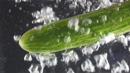 condimento : Green cucumber in boiling water with bubbles on black background, slow motion