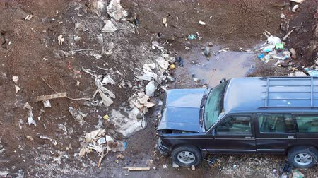 guba : Broken vehicle left on a garbage dump, spring, dirt, debris around the vehicle Stock mozgókép