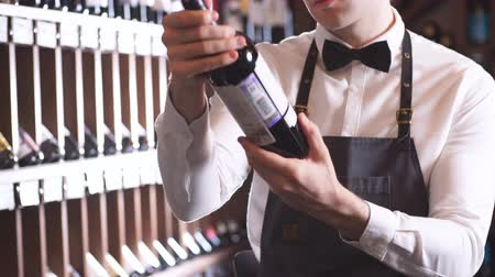 хрупкий : Handsome and young smiling brown haired sommelier with a bottle of wine on the background of dark wine house with shelves of bottles with alcohol Стоковые видеозаписи