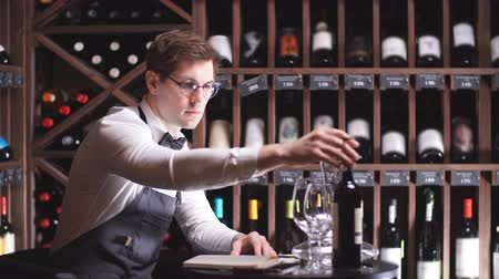 ware : Professional male cavist examines the bottles with wine in wine shop, holding wonderful sample, ready to speak out about this wine to customers Stock Footage