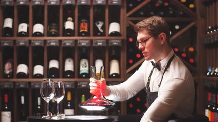 profesionálové : Wine taster or degustator mixing red wine into carafe to make perfect color on background with wine bottles racks in wine house.
