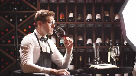 vinné sklepy : Bartender or male cavist standing near the shelves of wine bottles holds a glass of wine, looks at tint and smells flavor of wine in glass. Dostupné videozáznamy