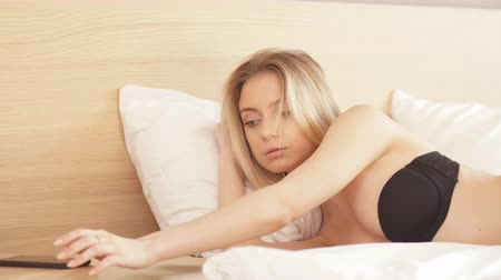 yatak kıyafeti : Seductive blond woman in black underwear lying on white bed. Youth and Tenderness. Relaxation concept