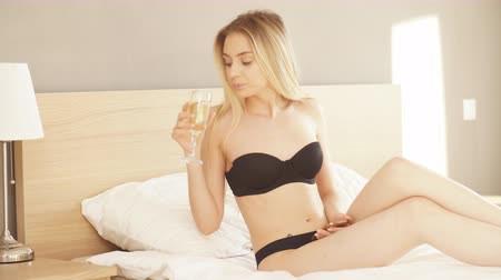 spojrzenie : Beautiful european woman with long blonde hair using her smartphone as she relaxing in bed in her underwear at day off Wideo