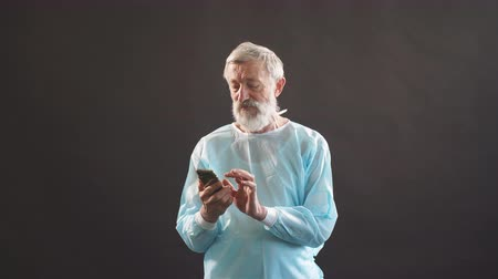 hromakey : Grey-haired experienced surgeon uses smartphone on dark background.