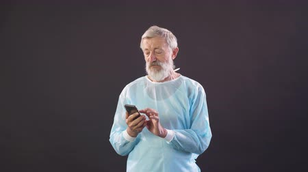 hromakey : Old doctor chatting on smartphone. Portrait of old man.