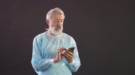 hromakey : Portrait of physician typing on smartphone. Dark screen chromakey background for keying.