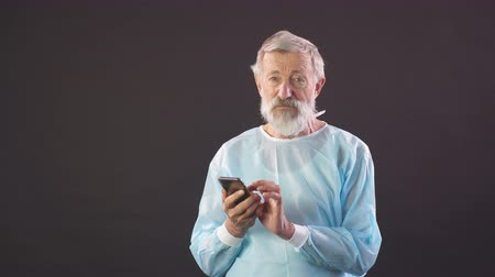hromakey : Old surgeon uses smartphone on dark background. Portrait of old man.