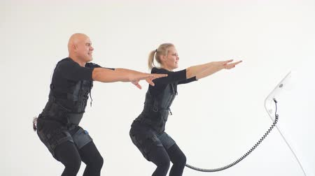 treinador : Man and woman in EMS suits developing core strength, family squatting with electrical muscle stimulation machine.