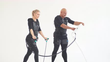electro : Motivated girl using expander during fitness training. Awesome girl working out with elastic expander while man controlling her, regulating her workout in sport club.