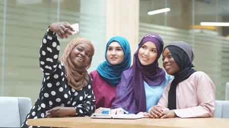 lenço : Group of four Asian and African Muslim women in fashionable traditional clothes taking selfie in shopping mall.