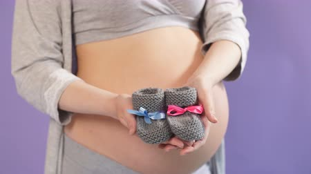 booties : Small booties for the unborn baby in the hands of pregnant woman on violet background.