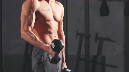 powerlifter : Shirtless sexy strong bodybuilder, athletic fitness man pumping up muscles with dumbbells in indoor gym workout against dark background. Stock Footage