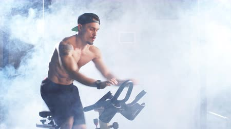 подготовке : Cardio Workout. Athletic man training on bicycle in gym. Sports guy is exercising on a stationary bike.