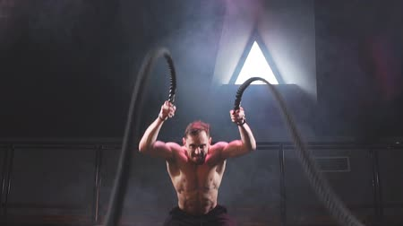 cross training : Caucasian bodybuilder practicing effective way to torch calories and enhance cardiovascular health. Full length photo. Battle rope training in a gym Stock Footage