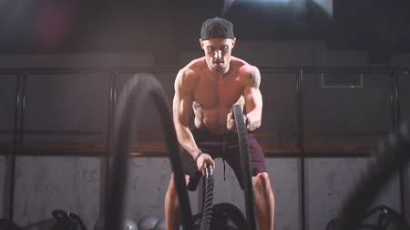 squatting : Shirtless strong athlete being concentrated on the exercise with battle rope requiring increased effort and strength, slow motion. Cross Fit concept.