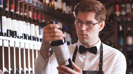steward : Young caucasian cavist dressed in white shirt and bowtie working in big vine shop presenting a bottle of red wine to customer Stock Footage