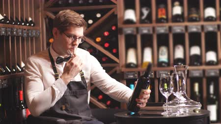 ösztönző : Elegant young sommelier with bow tie uncorking bottle of wine in wine boutique. Wine tasting social event.