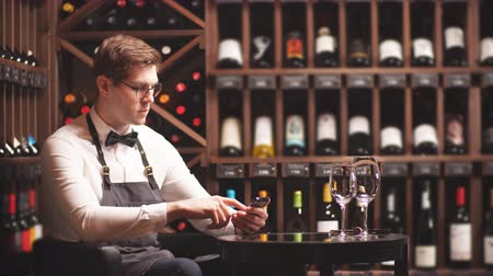 kelder : Beautiful young sommelier making notes in your smartphone to work in the wine boutique Stockvideo