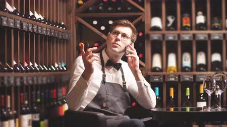 kelder : Elegant young sommelier talking on the phone with the buyer in a wine boutique