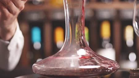 sommelier : Skilled sommelier pouring wine from decanter into wine glass. Degustation of wine process in wine boutique, close up. Stock Footage