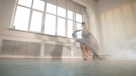 beige stof : Expressive video of female ballet dancer dressed in grey-blue flowing fabric spinning on one leg on white background. Stockvideo