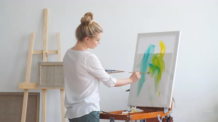 categoria : Young awesome cheerful girl enjoying painting at home. Spare time, pastime, interest