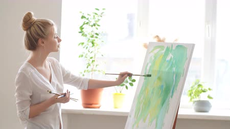 categoria : Light room for painting. Woman standing on the corner of the room in front of the easel Stock Footage