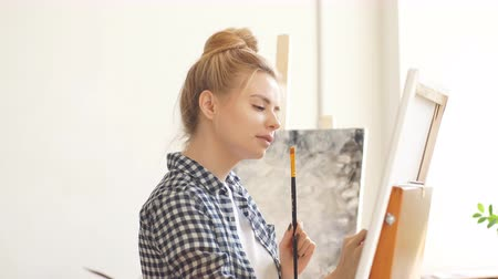 şövale : Funny blond girl with a brush in her hand using spatula to correct her art work.