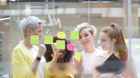 post it : Business, startup, people concept. creative glamour team writing on stickers at office glass wall. Stockvideo