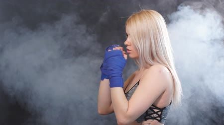 duruş : Beautiful determined blonde female boxer in blue handwraps getting prepared for big fight with smoky background. Sport, challenge victory, workout. Stok Video